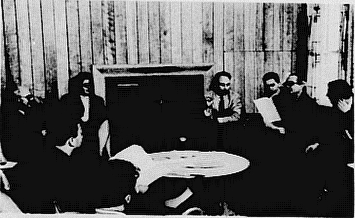 A group of 1960s academics sit in a circle