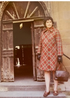 An image of Goldfarb in a red plaid coat standing at the top of some steps near a door
