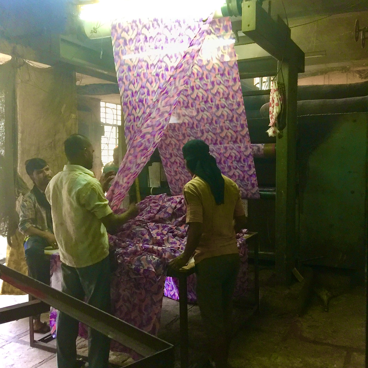 Three worker examine a sheet of fabric in a textile mill